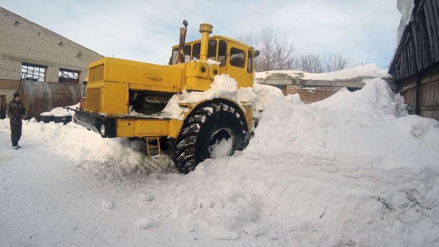 Старый трактор К-700 «Кировец» выбирается на дорогу из огромного сугроба