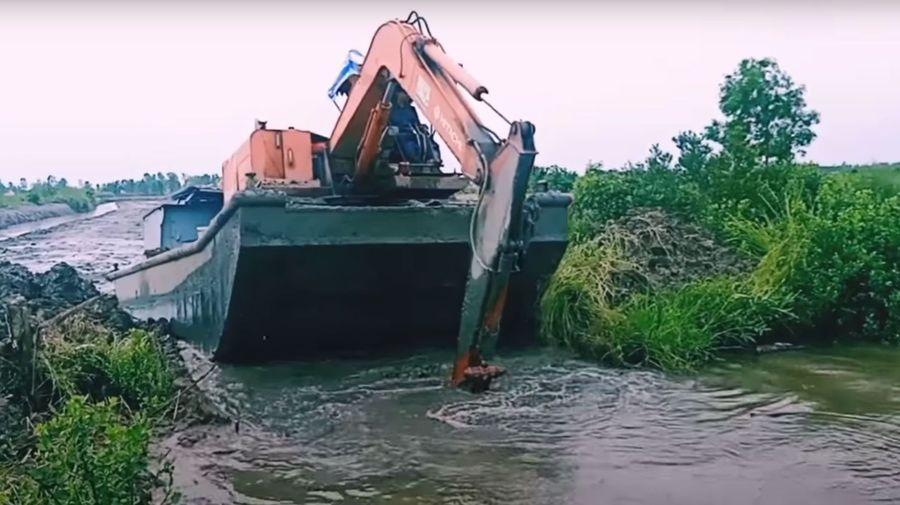 Посмотрите, как лодка, управляемая экскаватором, перебирается через земляной вал